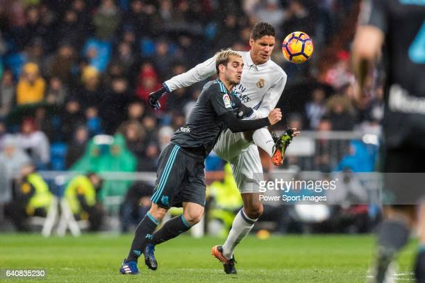 Juanmi Jimenez of Real Sociedad battles for the ball with Raphael Varane of Real Madrid in action during their La Liga match between Real Madrid and...