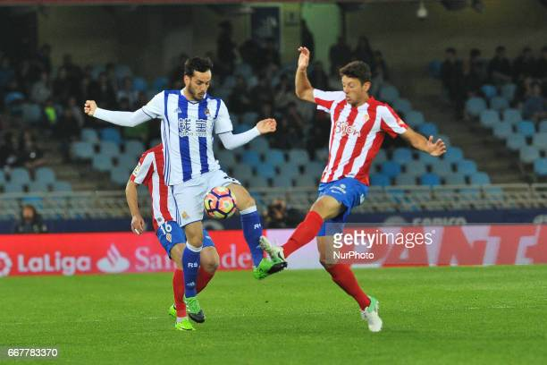 Juanmi of Real Sociedad duels for the ball with Jorge Mere of Sporting Gijon during the Spanish league football match between Real Sociedad and...