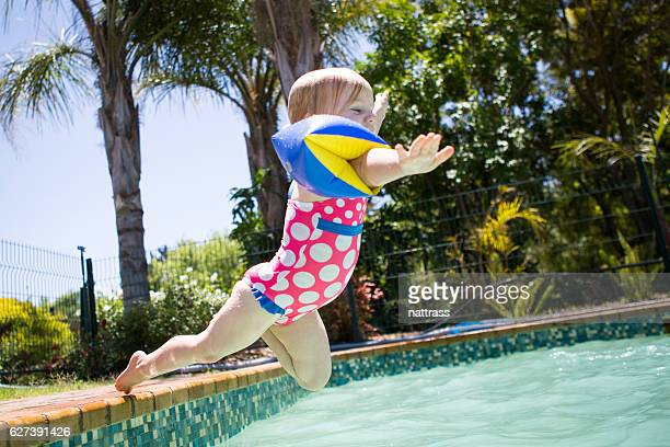 Jubilant baby girl jumps into the swimming pool