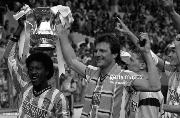 Jubilant Coventry City goal scoerers Dave Bennett and Keith Houchen hold the FA Cup aloft after beating Tottenham Hotspur in the final at Wembley