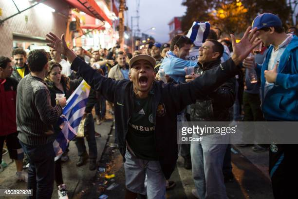 Jubilant fans of the Uruguay football team watching a television in a bar near the 'Arena de Sao Paulo' stadium celebrate after Luis Suarez scores...