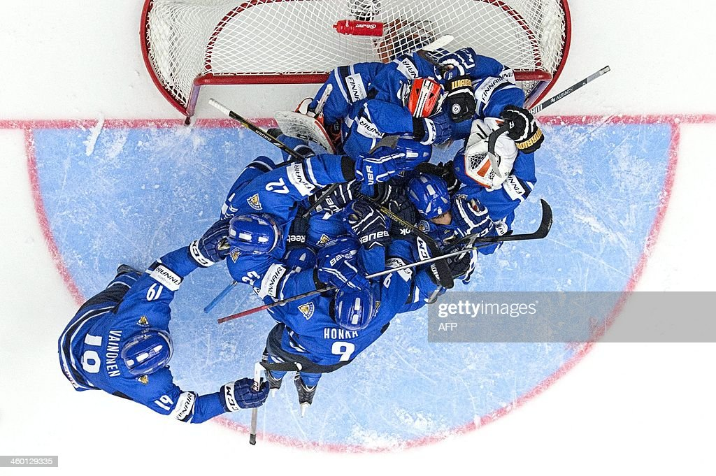 Jubilating Finnish players land in a heap on top of goalie Juuse Saros after the 5-3 victory in the World Junior Hockey Championships quarter final between Finland and Czech Republic at the Malmo Arena in Malmo, Sweden on January 2, 2014. AFP PHOTO / LUDVIG THUNMAN / SWEDEN OUT