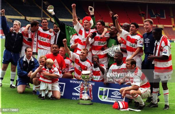 A jubilent Kingstonian team celebrate after their victory 10 over Forest Green Rovers in the Umbro FA Trophy at Wembley stadium in London
