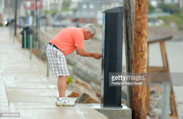 Jud Foy of New York attempts to use his credit card at a parking machine on Long Sands Beach in York on Tuesday June 20 2017 New parking meters along...