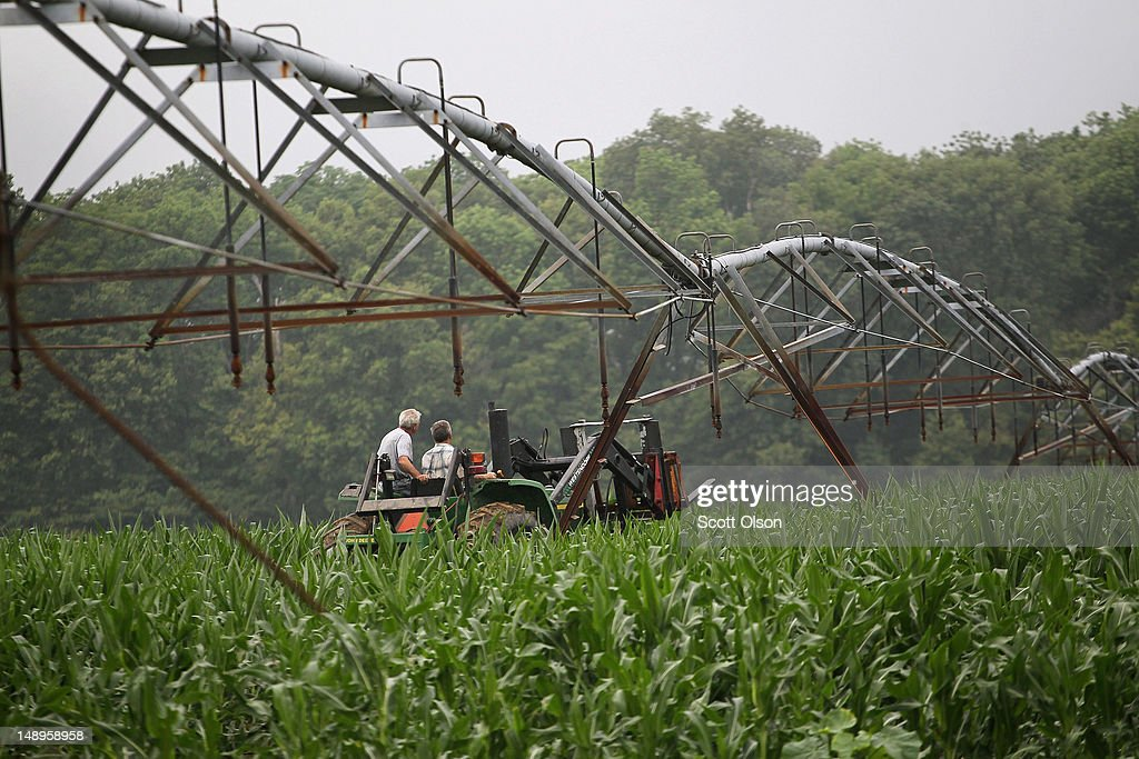 Jud Vaught (R) and his brother Bill Kirklin ride a tractor through their cornfield as they prepare to move their irrigation system to another part of the field on July 20, 2012 near Whiteland, Indiana. Kirklin and Vaught, who are 6th generation Indiana farmers, raise about 1,500 acres of corn and soybeans on a farm founded by their family in 1835. The corn and soybean belt in the middle of the nation is experiencing one of the worst droughts in more than five decades. Indiana was the nation's fourth largest corn producer in 2011.