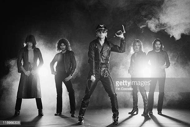 Judas Priest British heavy metal band pose against a dark background with smoke and light in a group studio portrait circa 1978