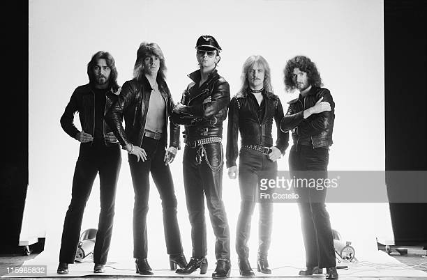Judas Priest British heavy metal band pose against a white background wearing black leather clothing in a group studio portrait circa 1978