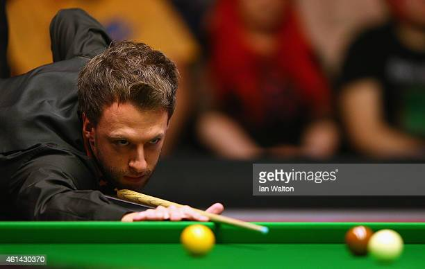 Judd Trump of England plays a shot during his first round match against Stephen Maguire of Scotland on day Two of the 2015 Dafabet Masters at...