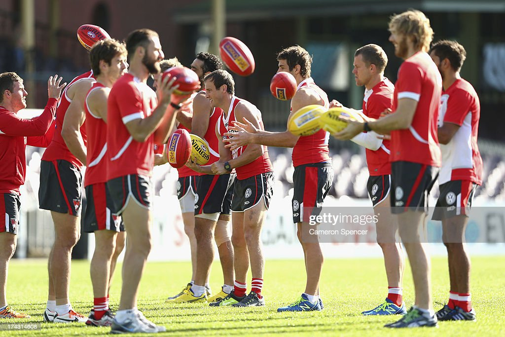 Jude Bolton of the Swans (C) and team mates warm up during a Sydney Swans AFL training session at Sydney Cricket Ground on July 24, 2013 in Sydney, Australia.