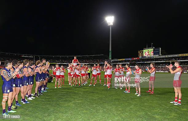 Jude Bolton of the Swans gets carried off by Jarrad Mcveigh and Ryan O'Keefe during the AFL Second Preliminary Final match between the Fremantle...