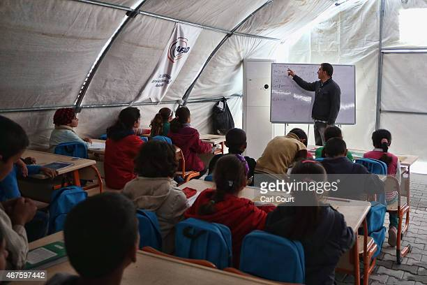 Judet Herjo a Syrian Kurd teacher from Kobani holds a lesson in a temporary classroom in Suruc refugee camp on March 25 2015 in Suruc Turkey The camp...