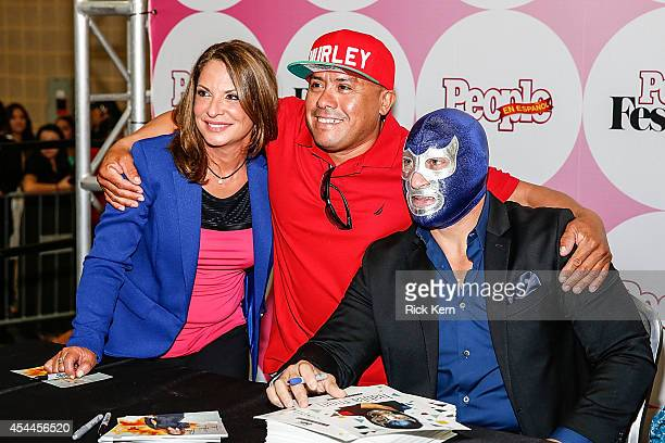 Judge Ana Maria Polo and luchador Blue Demon Jr pose for a photograph with a fan during HBO Latino Habla Men at People en Español San Antonio...