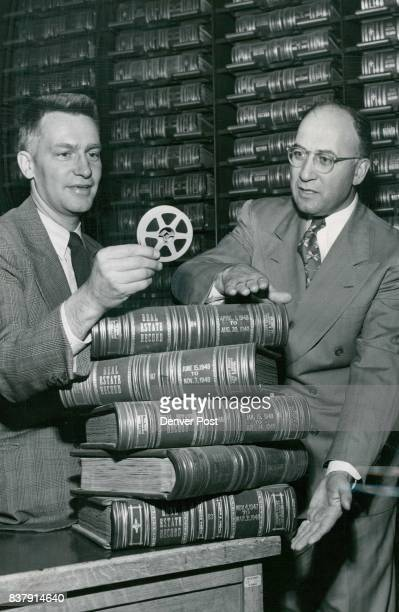 Judge David Brofman and clerk William Miller look at a reel of microfilm that contains as many pictures of court documents as are contained in the...