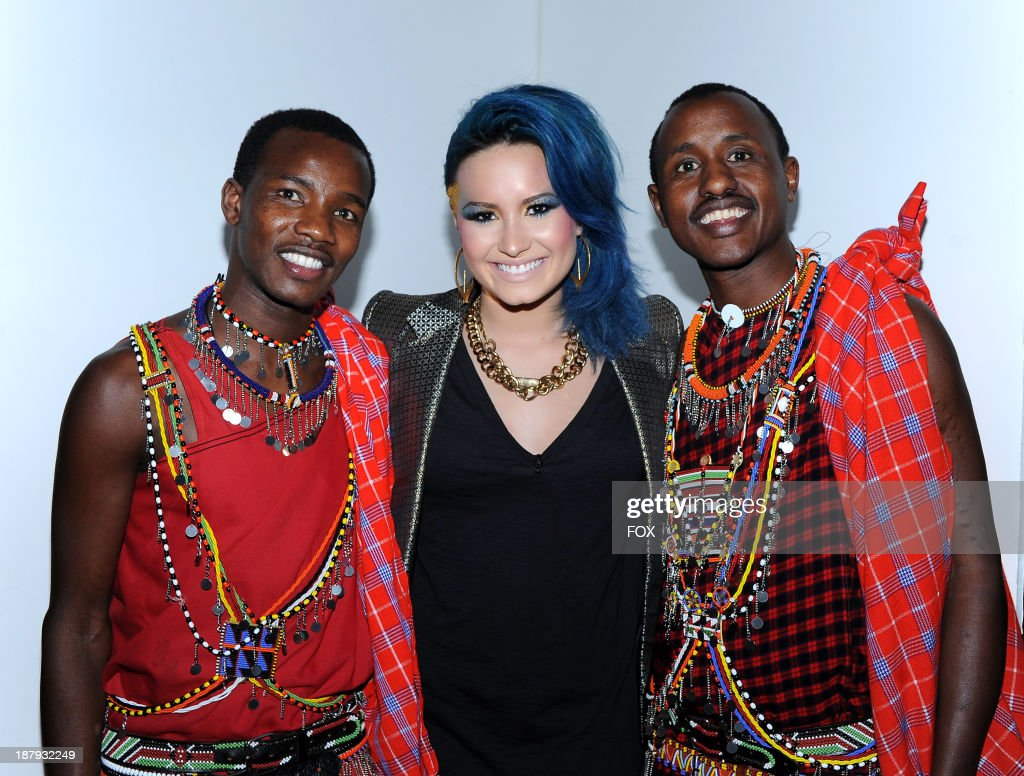 Judge <a gi-track='captionPersonalityLinkClicked' href=/galleries/search?phrase=Demi+Lovato&family=editorial&specificpeople=4897002 ng-click='$event.stopPropagation()'>Demi Lovato</a> (C) poses with her Maasai cultural guides from her volunteer trip to Kenya on FOX's 'The X Factor' Season 3 Top 13 To 12 And Top 12 Perform Live show on 80's night on November 13, 2013 in Hollywood, California.
