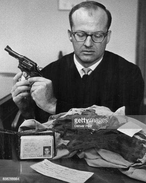 Judge Fullerton looks over evidence He holds a 38caliber revolver Before him is Knobbe's bloodstained shirt A driver's license a $32 check used to...
