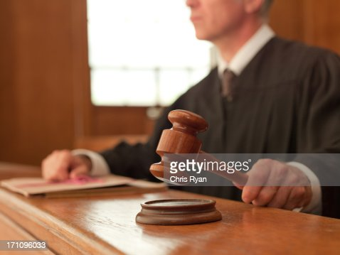 Judge holding gavel in courtroom