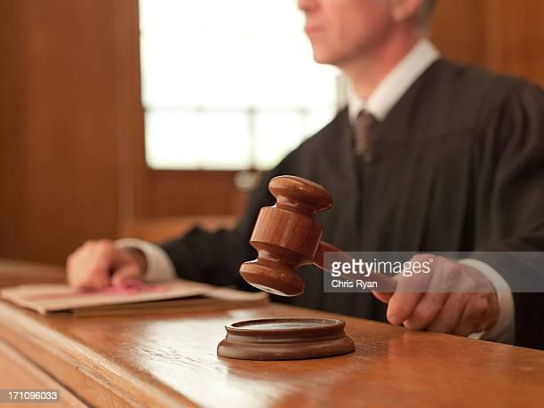 Richter holding Richterhammer im Gerichtssaal