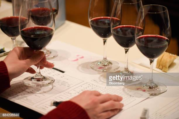 A judge holds a glass of wine as they are assessed at the 4th Sakura Japan Women's Wine Awards 2017 the international wine competition judged by...