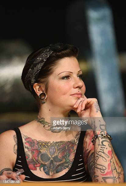A judge in the Tattoo Queen 2012 tattoo beauty competition sits on the panel at the 21st International Tattoo Convention Berlin on December 3 2011 in...