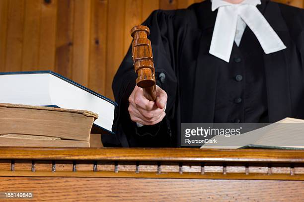 Judge In Traditional Court Robes Using the Gavel.