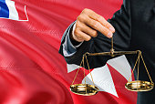 Judge is holding golden scales of justice with Wallis And Futuna waving flag background. Equality theme and legal concept.