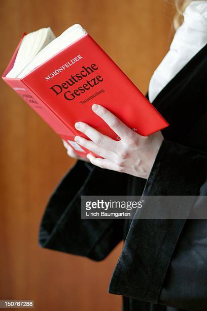 Judge / public prosecutor / lawyer wearing a robe holding the Schoenfelder code of law Deutsche Gesetze