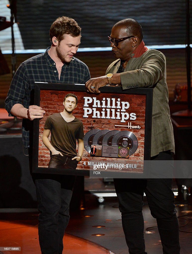 Judge Randy Jackson (R) presents Season 11 winner Philip Phillips (C) with a 4 million singles sold plaque onstage at FOX's 'American Idol' Season 12 Top 10 To 9 Live Elimination Show on March 14, 2013 in Hollywood, California.