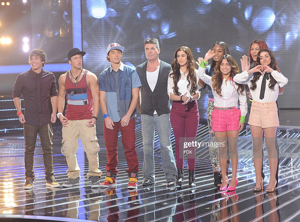 Judge Simon Cowell (C) and contestants Emblem3 (L) and Fifth Harmony onstage at FOX's 'The X Factor' Season 2 Top 10 Live Performance Show on November 21, 2012 in Hollywood, California.