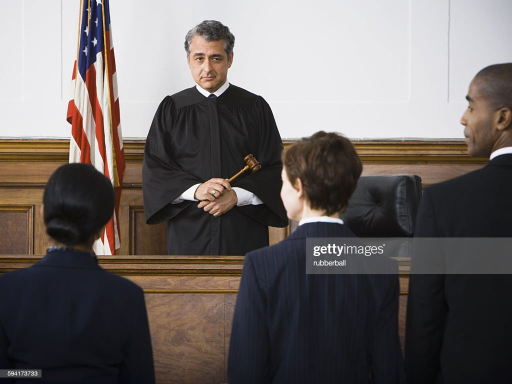 Judge standing in front of defendants and lawyers