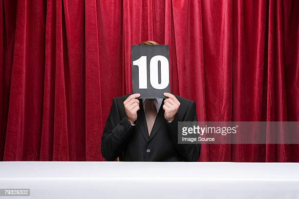 Judge with a score card covering his face