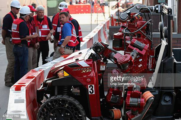 Judges and officials meet to decide how to proceed after Team Tartan Rescue's CHIMP robot crashed its vehicle during the driving task of the Defense...