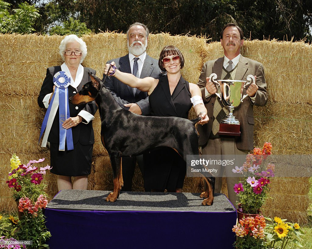 Judges and owner with winning Doberman Pinscher at dog show : Stock Photo