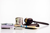 Judge's gavel and packs of dollars and euro banknotes on a white background. The concept of growing national debt- image