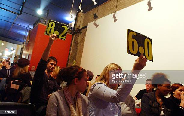 Judges hold up scores during a poetry slam at the Bowery Poetry Club December 6 2002 in New York City The Bowery Poetry Club which offers nightly...