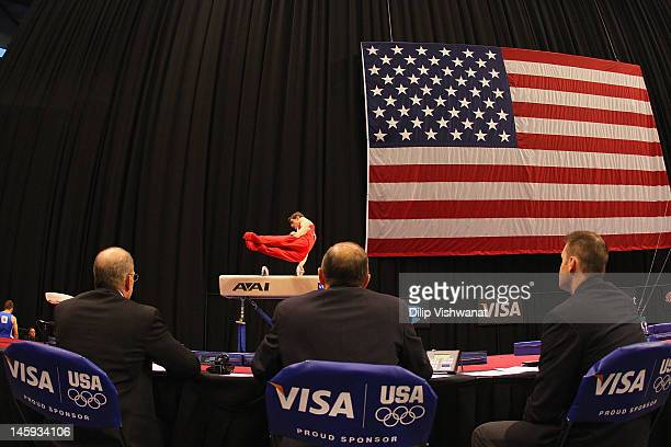 Judges watch Eric Schryver compete on the pummel horse during the Senior Men's competition on day one of the Visa Championships at Chaifetz Arena on...