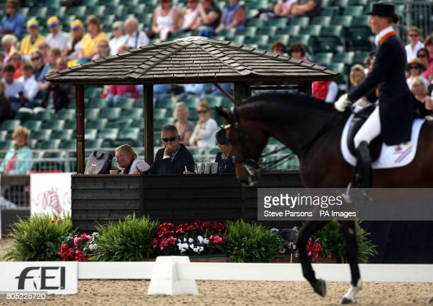 Judges watch Imke SchellekensBartels from Netherlands riding Hunter Douglas Sunrise as they compete during day one of The European Show Jumping and...