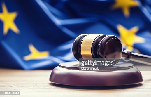 Judges wooden gavel with EU flag in the background. : Stock Photo