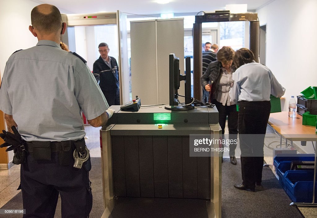 Judiciary employees operate security controls ahead of a trial against a former Auschwitz guard at the court in Detmold, western Germany, on February 11, 2016. The 94-year-old former Auschwitz guard went on trial for complicity in the murders of tens of thousands of people at the Nazi concentration camp. / AFP / POOL / Bernd Thissen