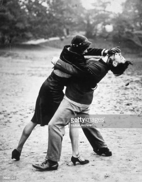 Judo experts Miss Phyllis Boutell and Mr C Cawhell giving a demonstration of self defence techniques on Hampstead Heath in London