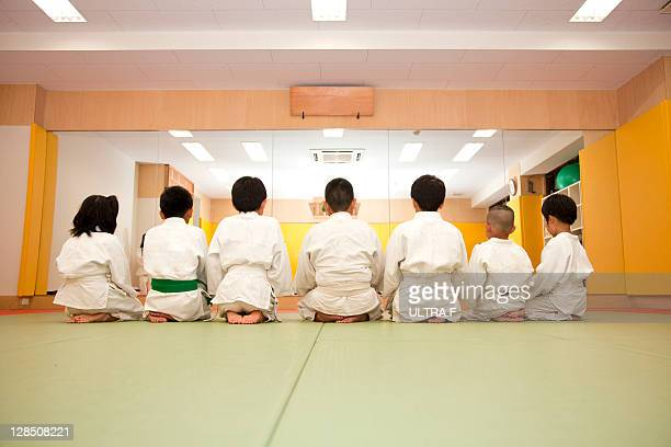 Judo players of the child sits down to one line