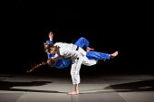 Two female black belt judo fighters throwing OSOTO GARI Position 3