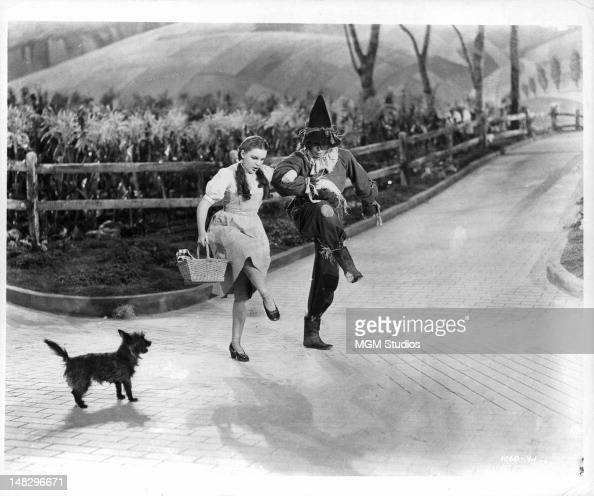 Judy Garland and Ray Bolger as the Scarecrow dance on the Yellow Brick Road as Toto watches in a scene from the film 'The Wizard Of Oz' 1939
