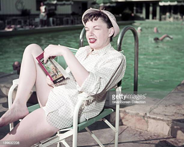 Judy Garland US singer and actress wearing a fine check shirt and shortbrimmed hat as she sits in a pool chair reading a book with a swimming pool in...