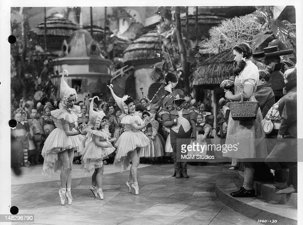 Judy Garland watch three munchkins dancing in a scene from the film 'The Wizard Of Oz' 1939