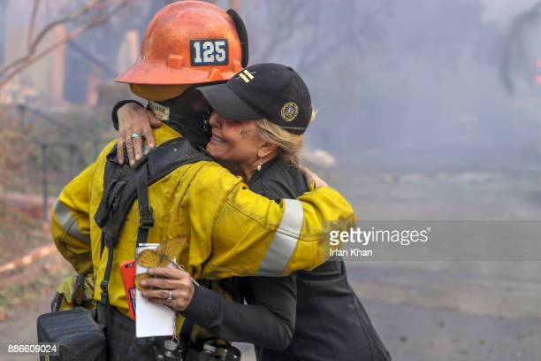 Judy HofmannSanders hugs a firefighter on McBroom Street in Shadow Hills where the Creek fire destroyed several homes