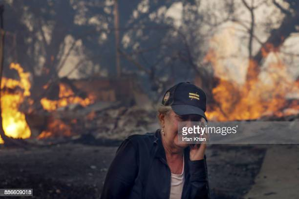 Judy HofmannSanders talks on the phone as her home is consumed by the Creek fire along McBroom Street in Shadow Hills