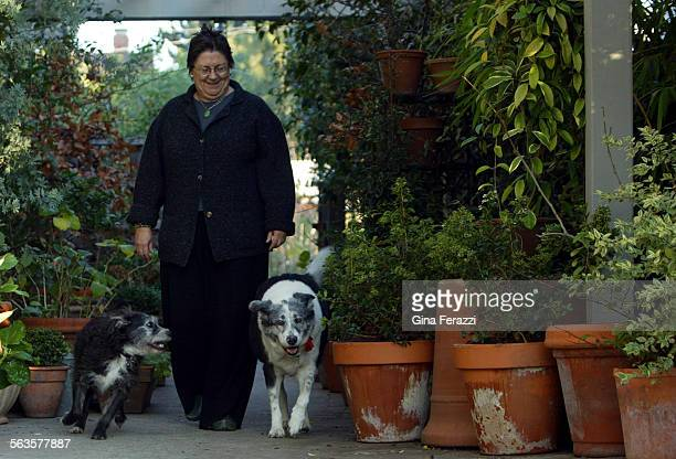 Judy Horton with her dogs Rose right and Bud walks under her side arbor filled with pots of Boxwood and Hydrangea plants in her winter garden in Los...