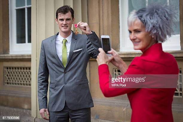 Judy Murray photographs her son Jamie Murray after he received his Officer of the Order of the British Empire for services to his sport and charity...