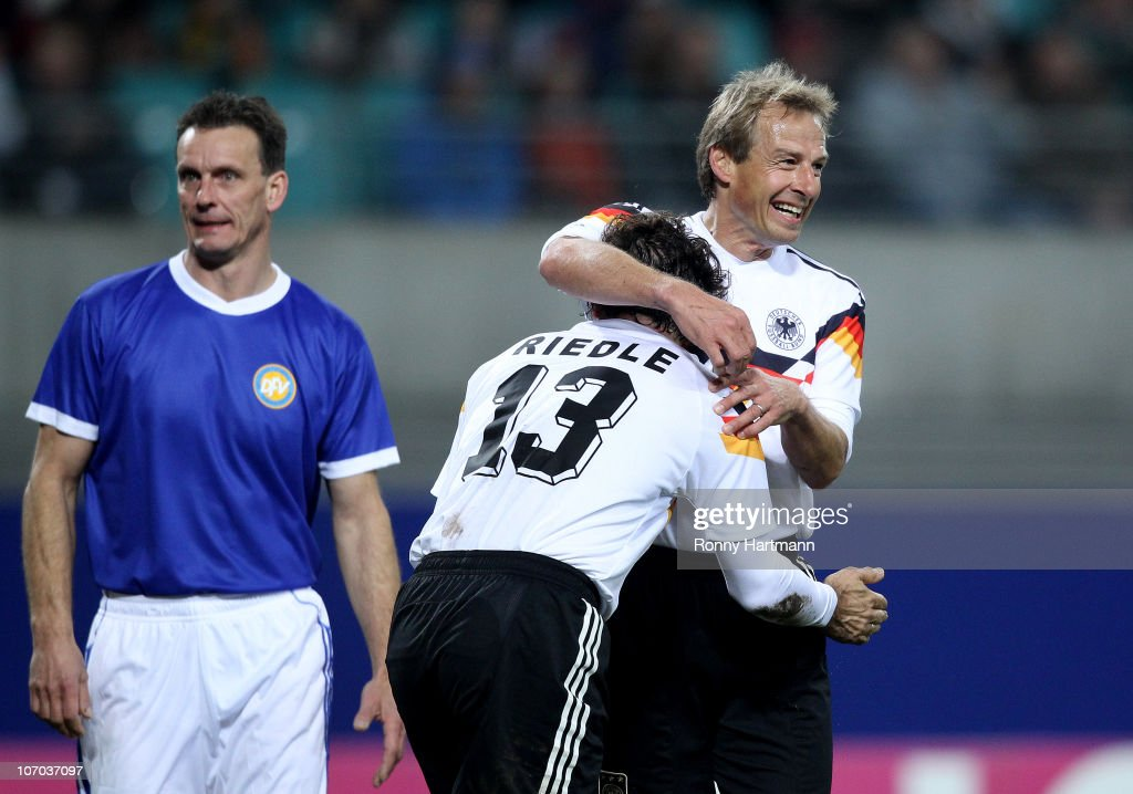 Juergen Klinsmann and Karlheinz Riedle of the World Champion 1990 celebrate their teams first goal next to Andreas Wagenhaus of the DFV Legend during the Reunification match between the World Champion 1990 and the DFV Legend at the Red Bull Arena on November 20, 2010 in Leipzig, Germany.