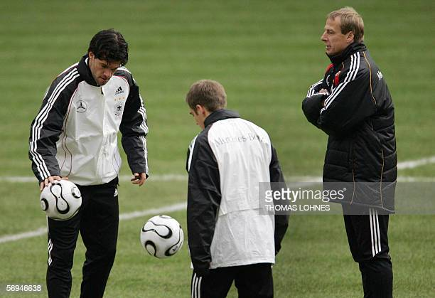 Juergen Klinsmann head coach of the German national football team observes his players Michael Ballack and Philipp Lahm during a training session 27...